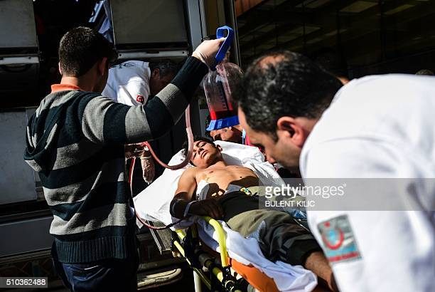 TOPSHOT An injured Syrian man arriving from northern Syria is carried to Kilis hospital in southcentral Turkey on February 15 2016 / AFP / BULENT...