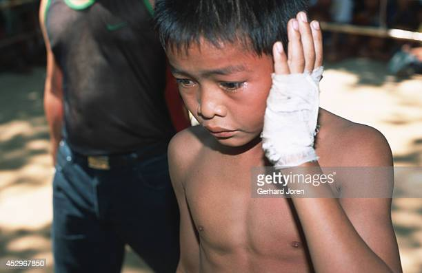 An injured Thai boxer who lost a fight against a Burmese at a Buddhist temple in Mae Kon Ken village close to the ThaiBurma border Adult bouts have...