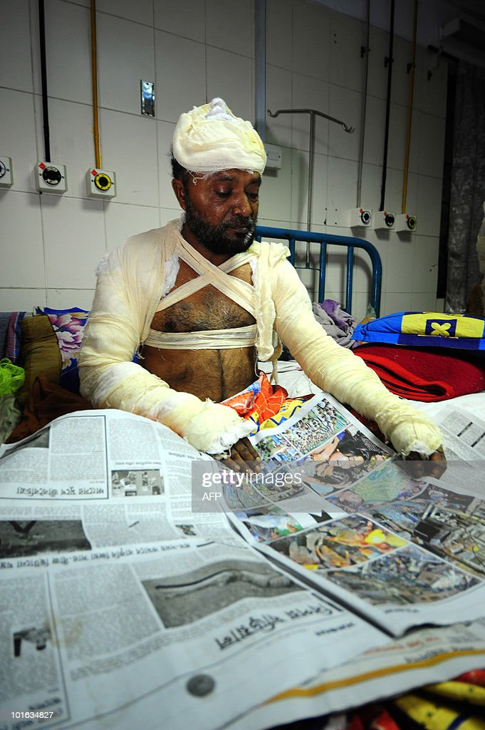 An injured victim of the Old Dhaka fire reads a newspaper at the Medical Hospital in Dhaka on June 5 , 2010. The national flag flew at half-mast and people of all faiths joined prayers as Bangladesh mourned the deaths of nearly 120 people in the country's deadliest blaze.