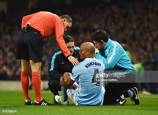 An injured Vincent Kompany of Manchester City is given treatment during the UEFA Champions League round of 16 second leg match between Manchester...