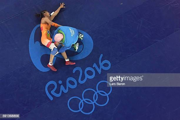 An injured Vinesh Vinesh of India is treated during a Women's Freestyle 48kg Quarterfinal bout against Yanan Sun of China on Day 12 of the Rio 2016...