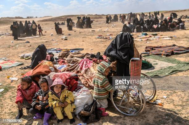 TOPSHOT An injured woman and her four children evacuated from the Islamic State group's embattled holdout of Baghouz sit at a screening area held by...