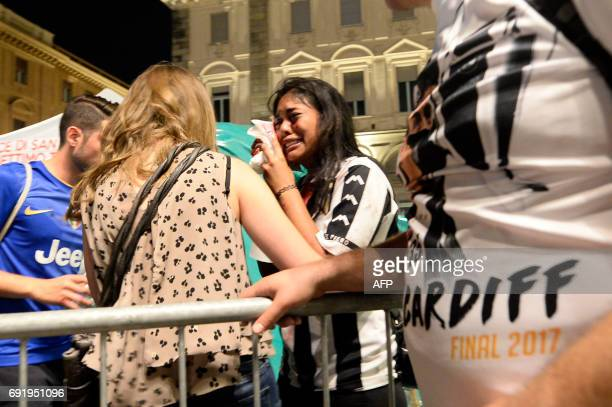 An injured woman cries at Piazza San Carlo after a panic movement in the fanzone where thousands of Juventus fans were watching the UEFA Champions...