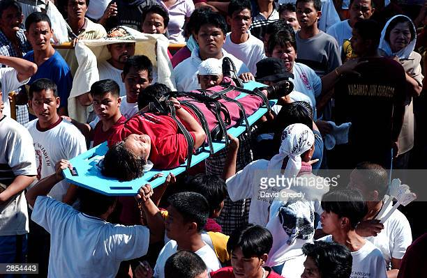 An injured woman is carried off during the annual procession of the Feast of the Black Nazarene January 9 2004 in the Philippine capital Manila...