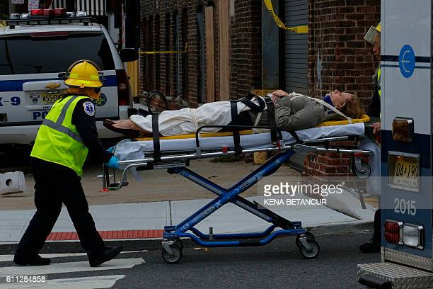 An injured woman is evacuated at New Jersey Transit's rail station in Hoboken New Jersey September 29 2016 A packed commuter train crashed into a...