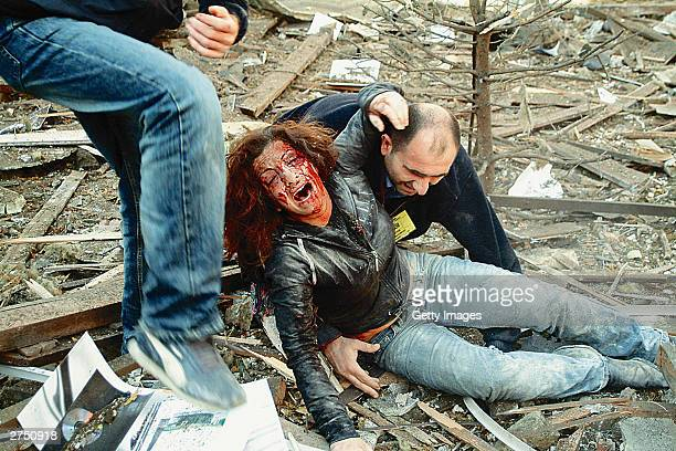 An injured woman is helped from the wreckage of a car bomb blast November 20 2003 which ripped through the British Consulate in Istanbul in this...