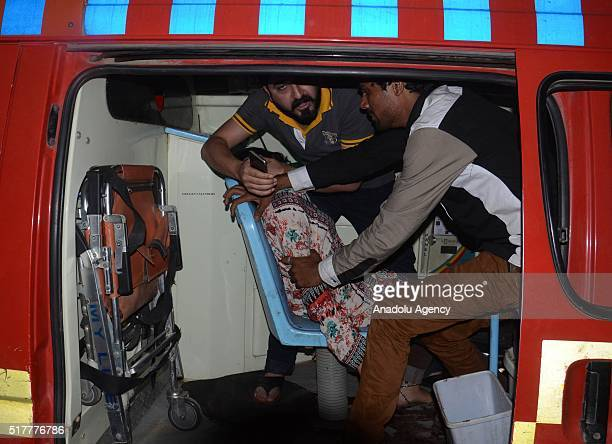 An injured woman is taken to a hospital after a suicide bomber blew himself up in a crowded park in Lahore killing at least 56 people and injuring...