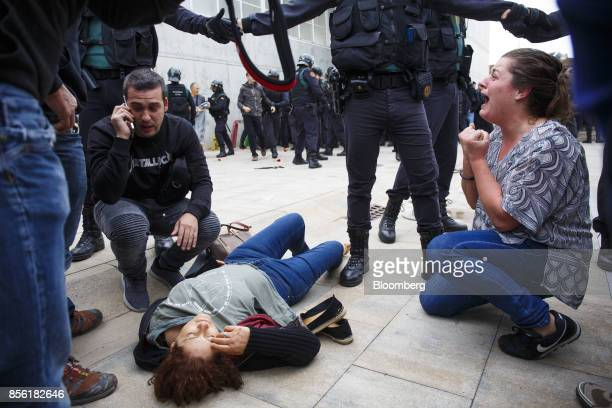 An injured woman lies on the ground following clashes between Civil Guard officers and members of the public outside a polling station used for the...