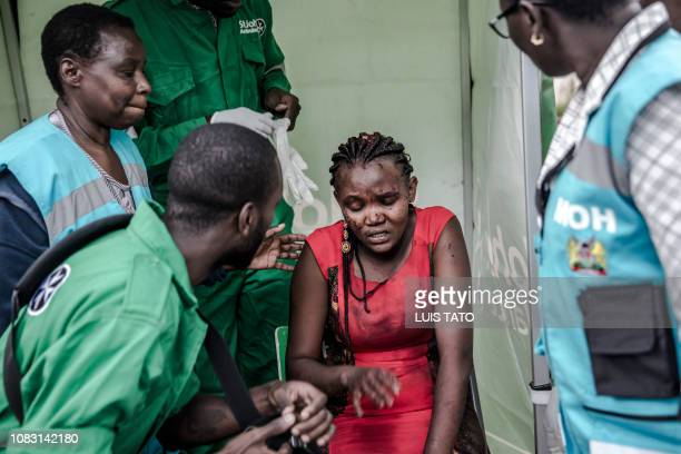 TOPSHOT An injured woman receives medical attention at the scene of an explosion at a hotel complex in Nairobi's Westlands suburb on January 15 in...