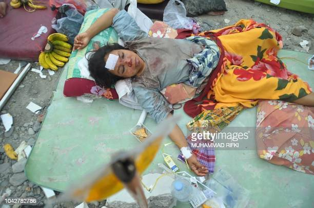 TOPSHOT An injured woman rests at a makeshift hospital after an earthquake and tsunami hit Palu on Sulawesi island on September 29 2018 Nearly 400...