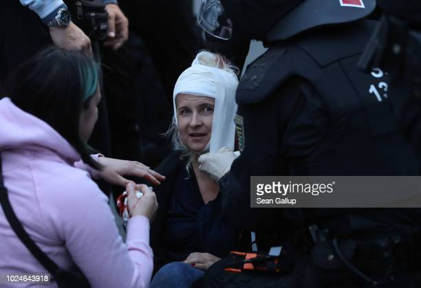 An injured woman who had been standing among rightwing supporters receives aid during a confrontation between rightwing and leftwing protesters the...