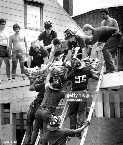 An injured workman is lowered to the street by EMTs and firemen after a minor accident at a house under construction on West Fifth Street in South...