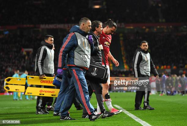 An injured Zlatan Ibrahimovic of Manchester United is given assistance during the UEFA Europa League quarter final second leg match between...