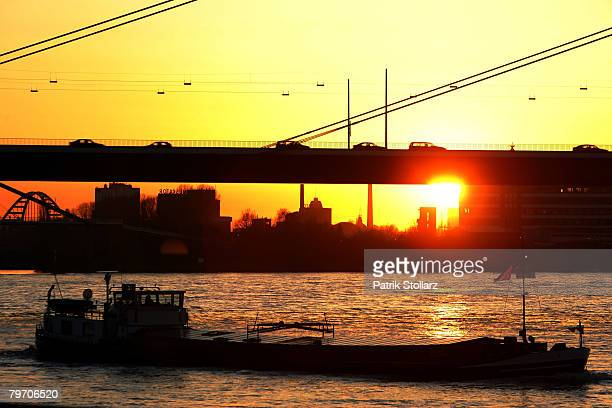 An inland ship goes on the Rhine River in the sundown on February 11 2008 in Duesseldorf GermanyThe weather is very mild for the winter month...