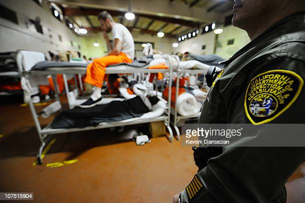 An inmate at Chino State Prison reads a book on his bunk bed as a California Department of Corrections officer looks on in a gymnasium that was...