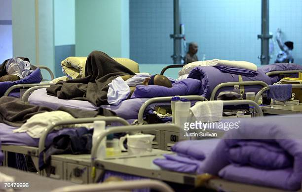An inmate at the Mule Creek State Prison sleeps on his bunk bed in a gymnasium that was modified to house prisoners August 28 2007 in Ione California...