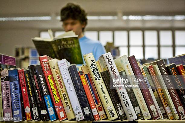 An inmate chooses a book from the prison library HMP Wandsworth London United Kingdom