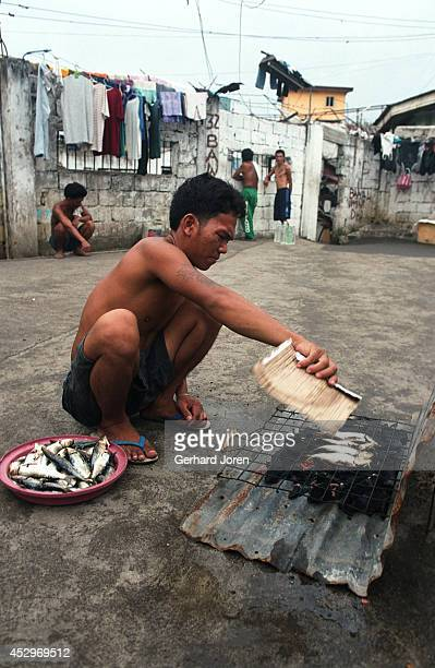 An inmate cooks fish for lunch at Manila City Jail. Manila City Jail was built for 800 prisoners by the Spanish in the mid nineteenth century, and...