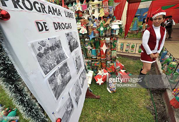 An inmate dressed as an elf stands next to the garden decoration at Santa Monica female detention center in Lima during a Christmas gastronomic...