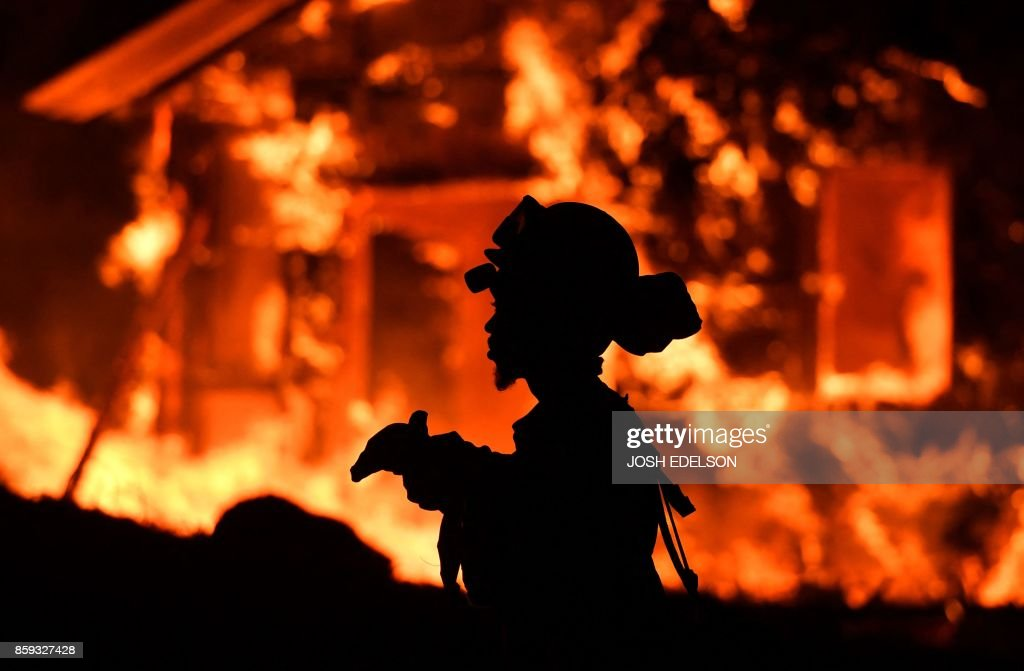 TOPSHOT - An inmate firefighter monitors flames as a house burns in the Napa wine region in California on October 9, 2017, as multiple wind-driven fires continue to whip through the region. /