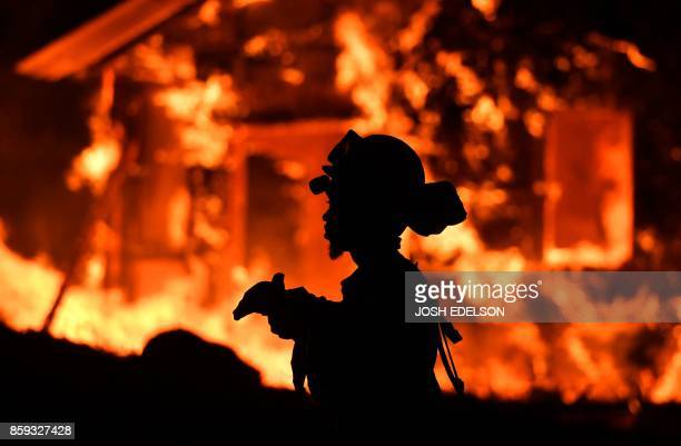 TOPSHOT An inmate firefighter monitors flames as a house burns in the Napa wine region in California on October 9 as multiple winddriven fires...