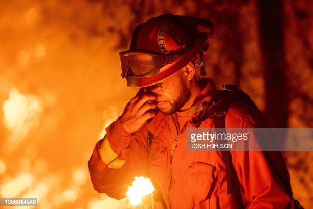 TOPSHOT An inmate firefighter pauses during a firing operation as the Carr fire continues to burn in Redding California on July 27 2018 One person...