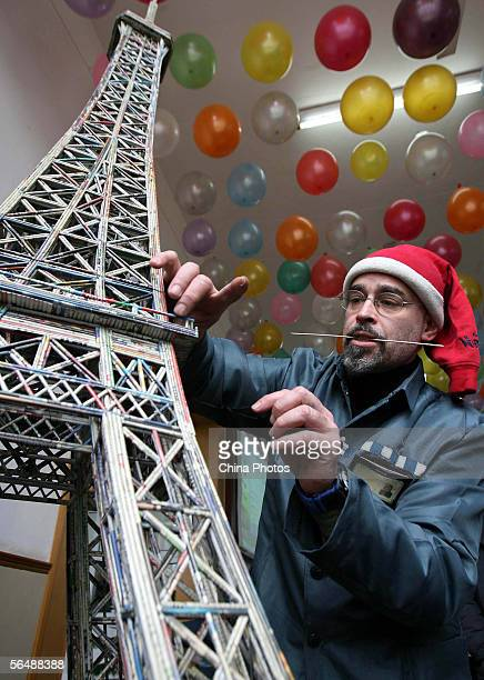 An inmate from Mexico decorates his craftwork a paper model of the Eiffel Tower for a handcraft works exhibition held to mark Christmas at the...