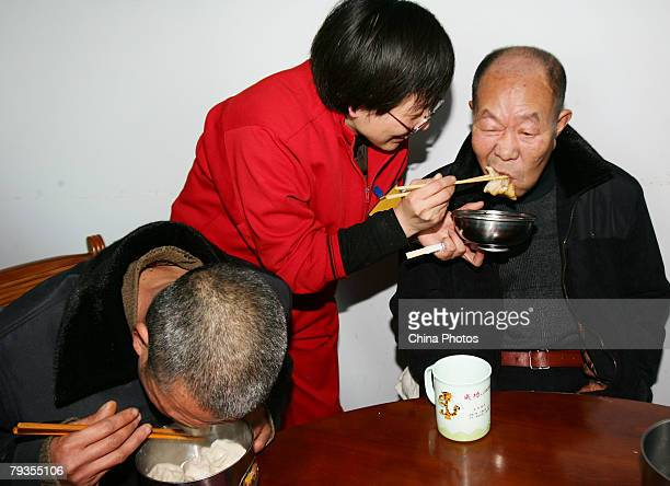 An inmate from the Changchun Women's Forced Labor Camp receives re-education through work as she feeds a senior citizen with a Chinese dumpling at...