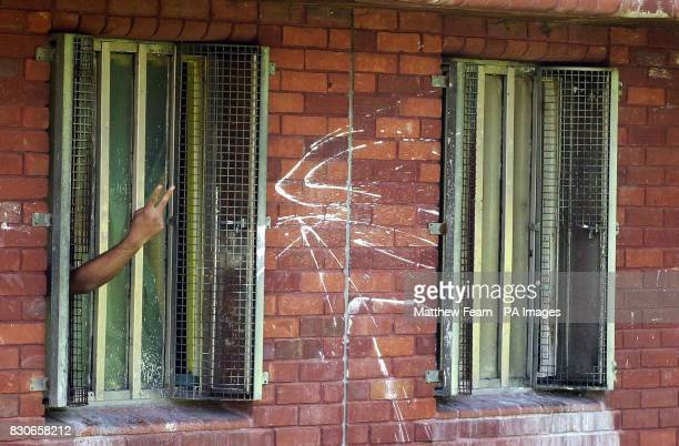 An inmate gestures through the bars of his cell window at HMP Feltham B Middlesex Young Offenders Institute