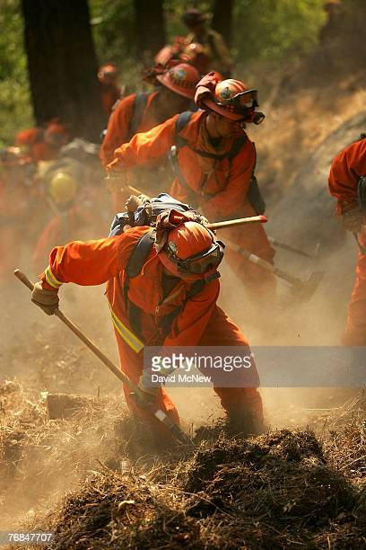 An inmate hand crew stirs up dust while building a fire break in case firefighters need to set a backfire to protect lakeside homes from the...