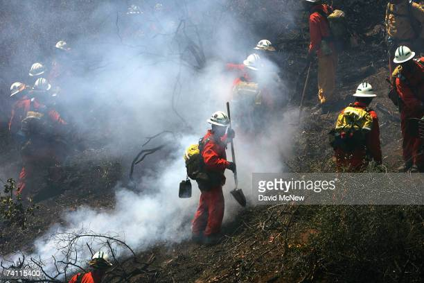 An inmate hand crew works to build a fireline around a wildfire in Griffith Park, the nation's largest urban park, on May 9, 2007 in Los Angeles,...