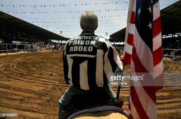 An inmate holds a US flag during the Angola Prison Rodeo at the Louisiana State Penitentiary April 23 2006 in Angola Louisiana The Angola Prison...