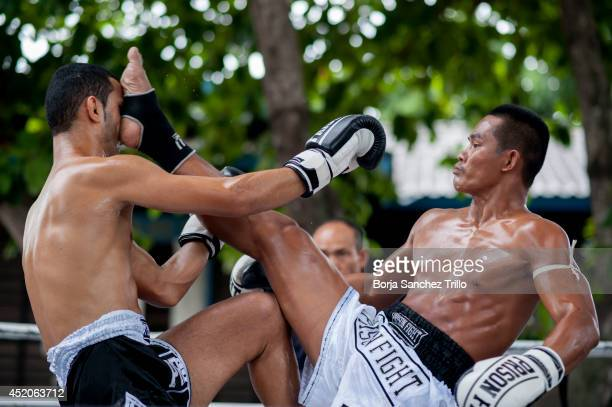An inmate kicks a foreigner fighter during a Muay Thai fight at Klong Pai prison on July 12 2014 in Nakhon Ratchasima Thailand Prison Fight is an...