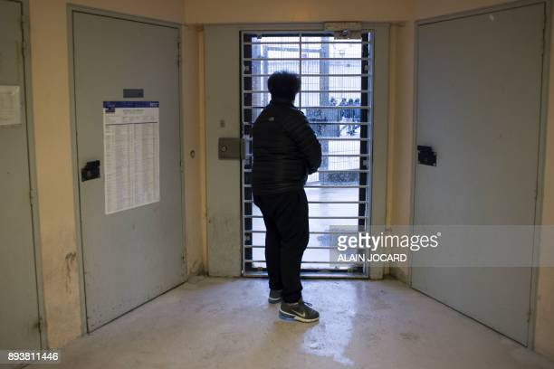 An inmate looks at other inmates walking in the courtyard of the prison of Meaux near Paris through a glazed door on December 15 2017 / AFP PHOTO /...