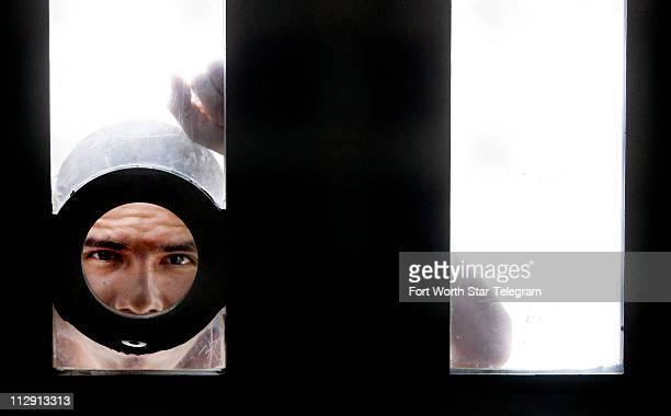 An inmate peers through a peep hole while in the exercise yard in solitary confinement at the Val Verde Correctional Facility in Del Rio Texas