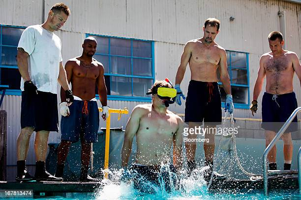 An inmate training to become a commercial underwater diver jumps into the pool blindfolded during a training exercise at the Marine Technology...