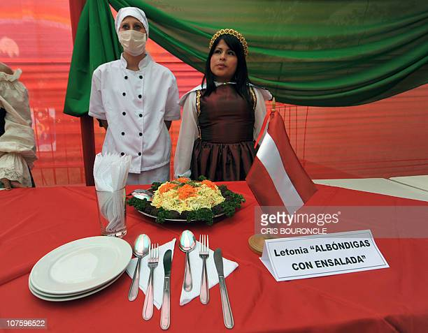An inmate wears a traditional Letonian attire as a traditional Letonian dish is displayed at Santa Monica female detention center in Lima during a...