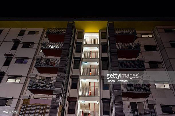 An inner city apartment block facade with windows and balconies at night.