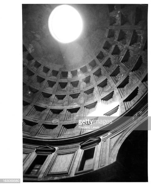 An inside view of the ornately built Roman Pantheon building looking up toward the light coming through the top of the dome in Rome Italy 1955
