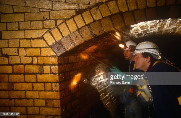 An inspection by the Thames Water Utilities sewer cleaning team looks closely at Victorianera brick wall linings of the Fleet River's Victorianbuilt...