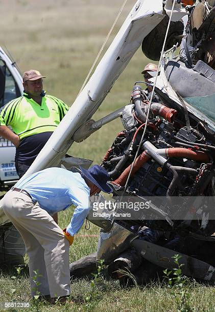 An inspector looks at a crashed Cessna 206 January 3 2006 in Ipswich Australia The aircraft crashed into a catchment dam on January 2 2006 after...