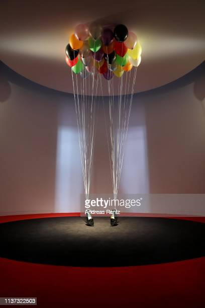 An installation by Appau Jnr BoakkyeYiadom with the title PYT shows shoes hang on ballons during the preview of the exhibition 'Michael Jackson On...