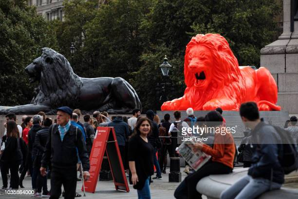 An installation featuring a bright red lion titled 'Please Feed The Lions' by British designer Es Devlin sits at the base of Nelson's Column beside...