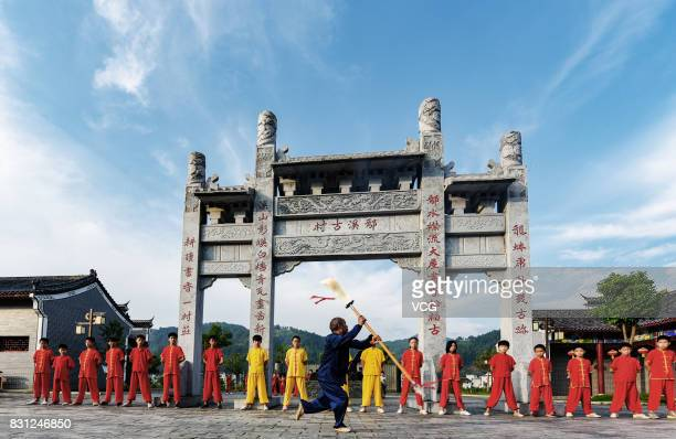 JI'AN CHINA AUGUST 13 An instructor and children from a Shaolin martial art institute practise kung fu at a village in Suichuan County on August 13...
