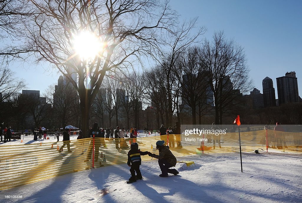 An instructor assists a child with a snowboard at the Winter Jam in Central Park on January 26, 2013 in New York City. The annual festival brings skiing, snowboarding and snowshoeing to New Yorkers with free equipment.