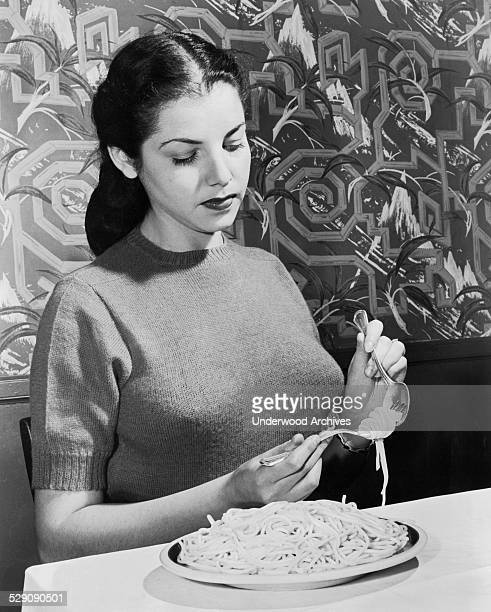 An instructor at the Foods Institute demonstrates the correct way eat spaghetti using a fork and soup spoon June 1948