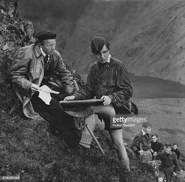 An instructor from the Sea School's course at the Aberdovey Outward Bound School asks one of his students to pinpoint their position on a map during...