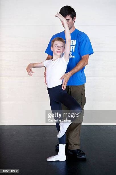 An instructor helping a young boy with ballet
