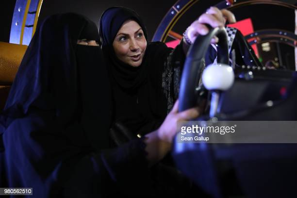 An instructor helps a woman who is wearing a traditional Muslim niqab to try out a car driving simulator during an outdoor educational driving event...