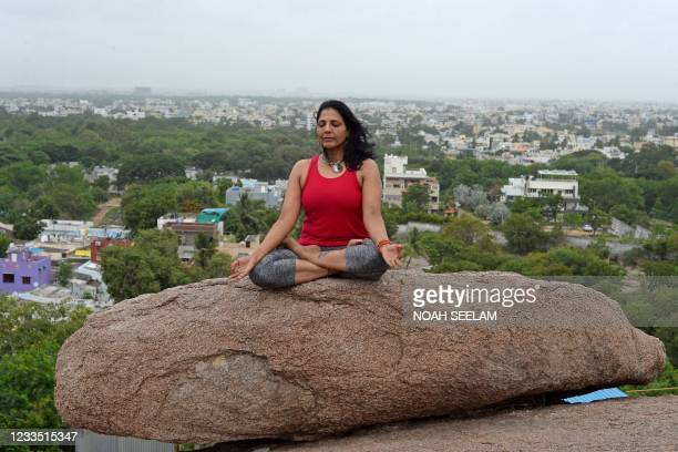 An instructor performs Yoga ahead of the International Yoga day atop rock formations overlooking the city at the Gun rock hills in Hyderabad on June...